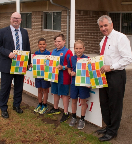 Professionals Outer Western Sydney principal Terry Hansen (far right) presents Bennett Road Public School principal Glen Leaf and students Beau Warren-Tibbets, Ricky Crow and Tyler Birnie with useful multiplication tables. Photo: David Taylor