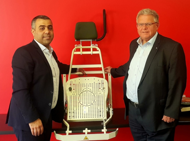 	Jason Elias, Managing Director, Precision Metal Group, with Reiner Ley, Senior Vice President, Rheinmetall Land system, with a prototype of the blast attenuated seating for the BOXER 8x8 CRV.